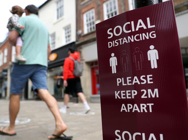People walk past a social distancing sign, ahead of the re-opening of non-essential retailers in England on June 15. Photo: PA