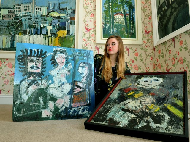 Scarlett Stewart, a curator at Harrogate's 108 Fine Art, with an example of paintings by Joash Woodrow at a previous exhibition at the gallery.