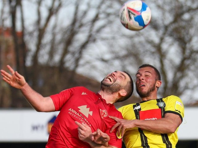 Harrogate Town striker Aaron Martin competes in the air with Morecambe's Alex Kenyon. Pictures: Matt Kirkham