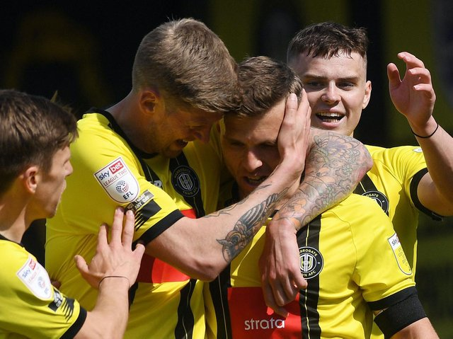 Jon Stead embraces strike partner Jack Muldoon after the latter opened the scoring during Harrogate Town's win over Bradford City. Pictures: Jonathan Gawthorpe