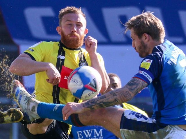 George Thomson competes for the ball with Carlisle United's Nick Anderton. Pictures: Matt Kirkham