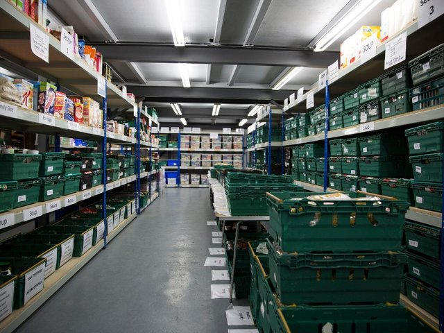 Shelving full of food to distribute at a foodbank.