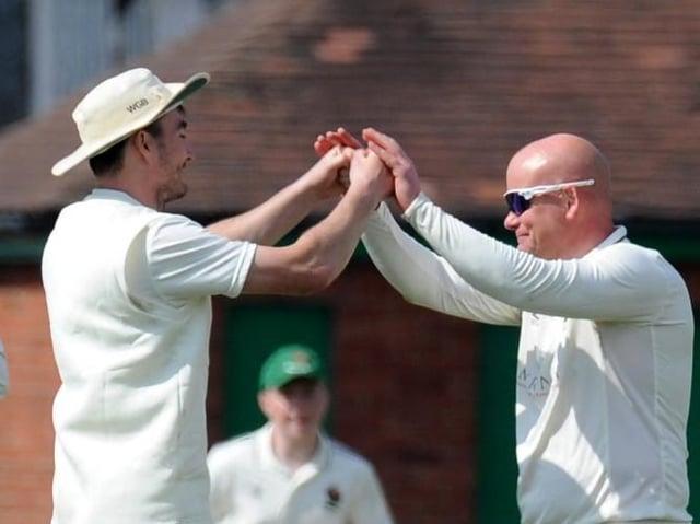 Harrogate CC skipper Will Bates, left, congratulates spinner Dominic Bradburne, who took three wickets during Saturday's win against York. Picture: Gerard Binks