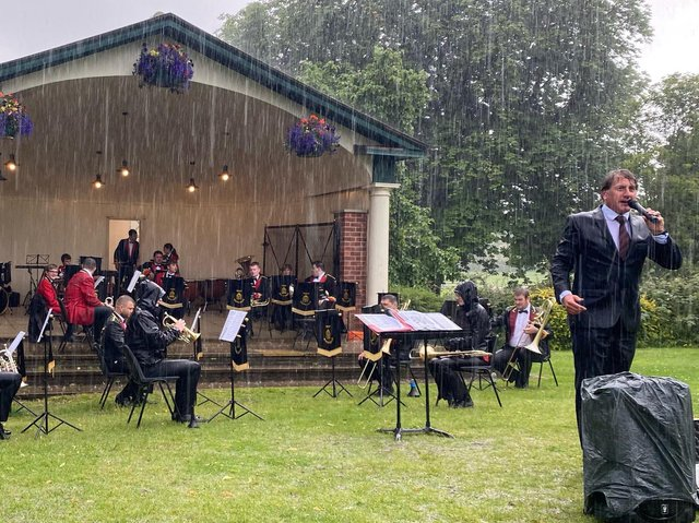 Tewit Youth Band and its Musical Director, Martin Hall bravely play on in a thunderstorm at the Valley Gardens in Harrogate.
