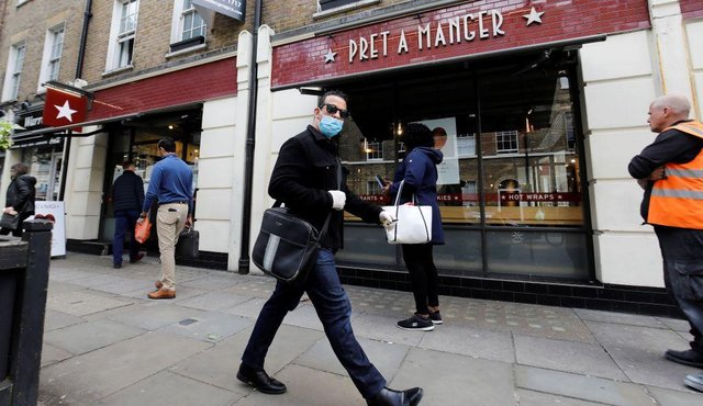 A man wearing PPE (personal protective equipment) passes customers queuing to enter a recently re-opened Pret-A-Manger shop which had originally closed-down due to the COVID-19 pandemic in London (Photo: TOLGA AKMEN/AFP via Getty Images)