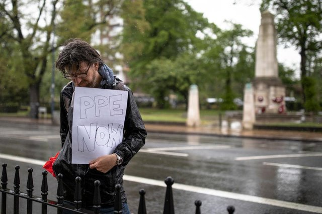 A man holds a sign relating to the lack of PPE equipment for frontline NHS staff during a minute's silence outside Lewisham Hospital (Photo: Dan Kitwood/Getty Images)